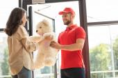happy girl receiving teddy bear from bearded man in cap
