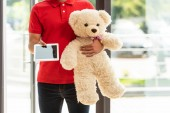 Photo cropped view of delivery man holding soft toy and digital tablet