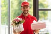 Veselý vousatý muž držící květiny a růžový Dárkový box