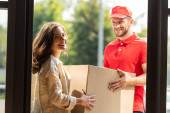 Photo cheerful delivery man in cap looking at camera and holding box near woman