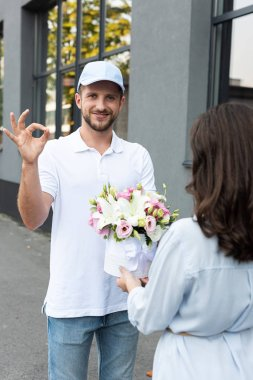 selective focus of happy delivery man in cap showing ok sign near woman with flowers
