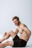 širý vousatý sportovec s bolestivou bolestí zad na šedé