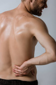 oříznutý pohled na širý sportovec s bolestivou bolestí vzadu izolovaný na šedé