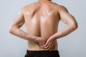pohled na širý sportovec se spodní bolestí v zádech izolovaný na šedé