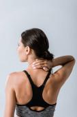 retro vista della sportiva con dolore al collo isolato sul grigio