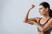 Photo attractive brunette sportswoman touching muscle isolated on grey