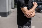 vista cropped dello sportivo in t-shirt nera con dolore al gomito sulla strada