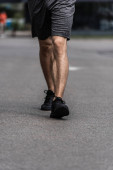 Photo partial view of sportsman in black sneakers walking on street
