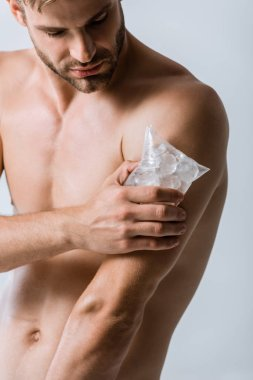 shirtless man using ice for shoulder isolated on grey