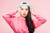 attractive asian woman in pullover and cap listening music isolated on pink