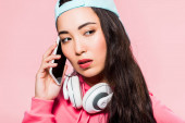 attractive asian woman in pullover and cap with headphones talking on smartphone isolated on pink