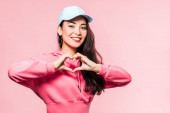 attractive asian woman in pink pullover and cap smiling and showing heart symbol isolated on pink