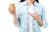 cropped view of woman in denim shirt pointing with hand at paper cup isolated on white