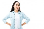 attraktive und lächelnde asiatische Frau im Jeanshemd zwinkert vereinzelt auf weißem Grund