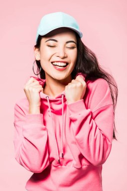 Attractive asian woman with closed eyes in pink pullover and cap smiling isolated on pink stock vector