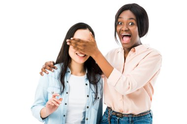 smiling african american woman obscuring face of her friend isolated on white