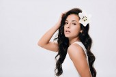 brunette beautiful woman with lily in long healthy hair isolated on grey