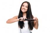 usmívající se bruneta krásná žena narovnávání dlouhých lesklých vlasů s plochým železem izolovaným na bílém