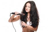 Fotografie usmívající se bruneta krásná žena stylizovaná vlnité vlasy s plochým železem izolovaným na bílém