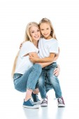 happy mother and daughter hugging and looking at camera on white