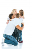 šťastní rodiče s úsměvem při objímání roztomilé děti na bílém