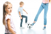 Photo selective focus of sad kid looking at camera near child playing football with mother isolated on white