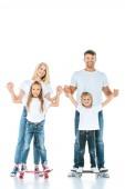 šťastní rodiče drží za ruce syna a dceru na koni penny desky na bílém