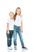 happy sister and brother in jeans standing on white