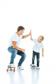 happy father giving high five to cheerful son riding penny board on white