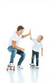 šťastný otec dává vysoké pět veselý syn na koni penny palubě na bílém