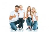 šťastní rodiče a děti ukazující palce na bílém