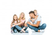 happy parents and children in blue jeans sitting on white