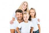 šťastná rodina v bílých tričkách při pohledu na kameru a s úsměvem izolované na bílém