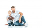 cute son holding rugby ball and sitting with happy father on white