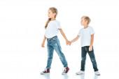dvě roztomilé děti se drží za ruce a chodí na bílém