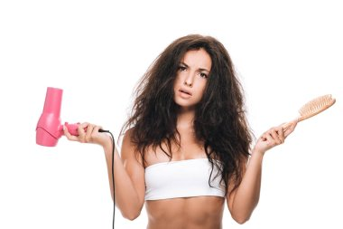 confused brunette beautiful woman with curly hair holding pink hairdryer and comb isolated on white
