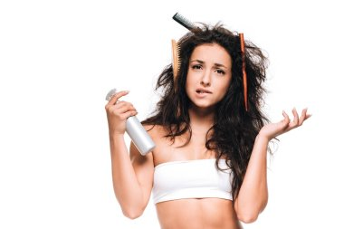 Confused brunette woman with combs in wavy unruly hair holding spray isolated on white stock vector