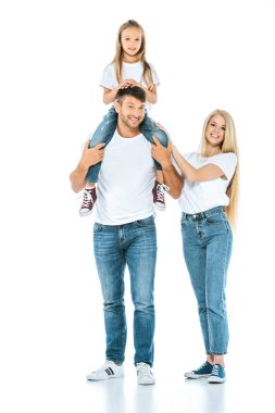 happy man holding daughter on shoulders near beautiful wife on white