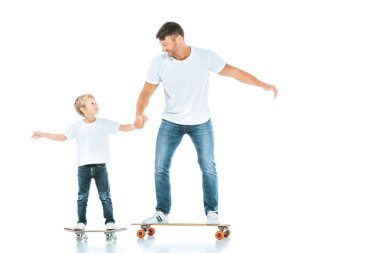 Happy father and son holding hands while riding penny boards on white stock vector