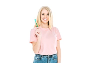 cheerful woman smiling while holding toothbrush isolated on white