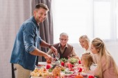 family members sitting at table and father cutting tasty turkey in Thanksgiving day