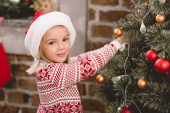 cute kid in santa hat and sweater decorating christmas tree