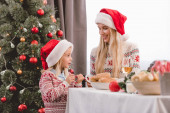 mother and daughter in sweaters and santa hats smiling and talking in Christmas