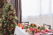 Fotografie plate with tasty turkey, corn, candy canes, candles, gift and wine glasses on table and christmas tree