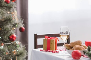 selective focus of wine glass, pies and christmas gift on table