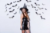 Photo smiling girl in black witch Halloween costume near white wall with decorative bats