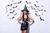 dívka v černé čarodějnice Halloween kostým s rukama na bocích v blízkosti bílé stěny s dekorativními netopýry