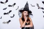 dívka v černé čarodějnice Halloween kostým při pohledu na kameru v blízkosti bílé zdi s dekorativními netopýry