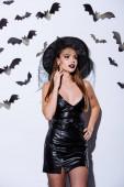 dívka v černé čarodějnice Halloween kostým v blízkosti bílé zdi s dekorativními netopýry