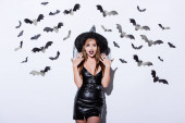 girl in black witch Halloween costume with open mouth near white wall with decorative bats